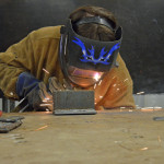 A student at a vocational high school in Massachusetts learns to weld. (Photo: Emily Hanford)